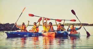 A group of 7 people raising their hands while on a kayak