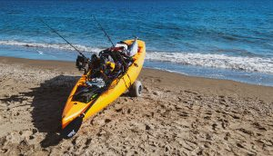 A kayak on the beach filled with accessories