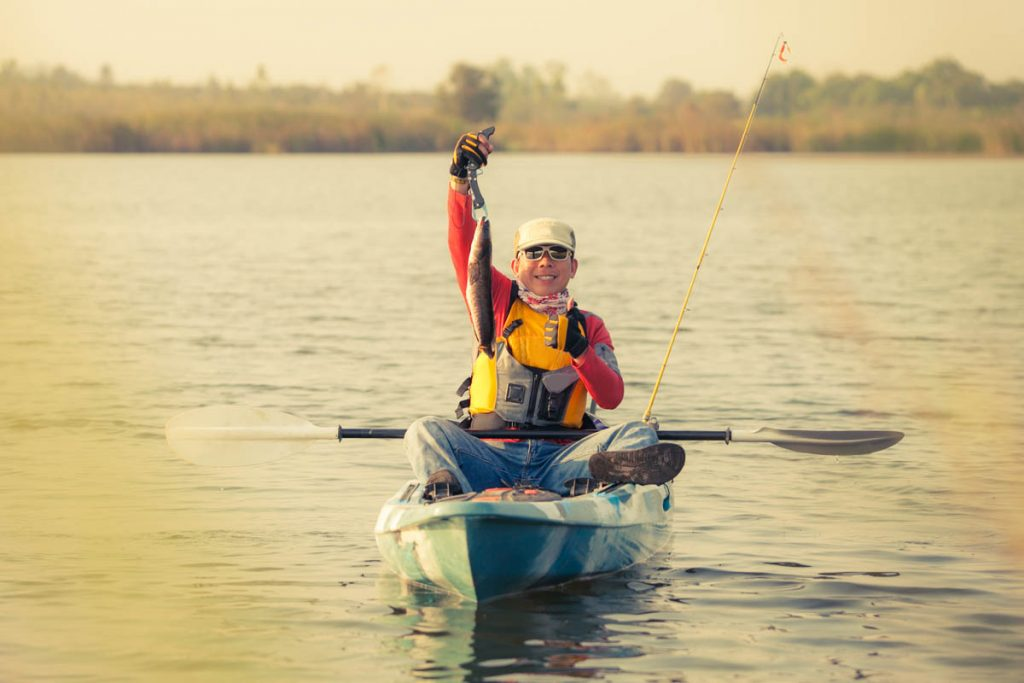 Person sitting on a fishing kayak with fish in right hand