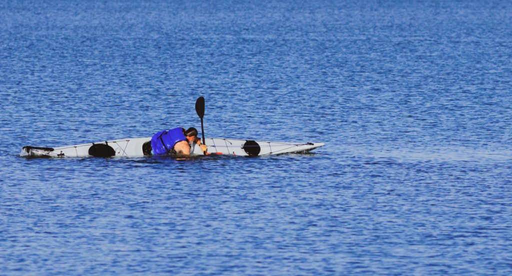 A person performing a sea kayak roll in the water