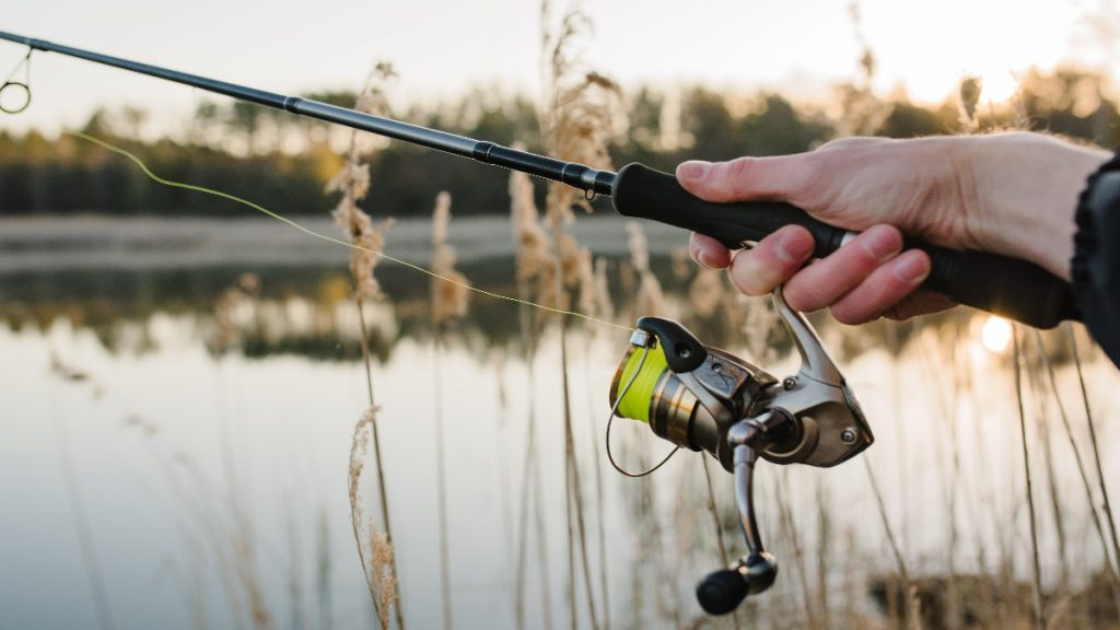 Person learning how to use a spinning rod in front of water