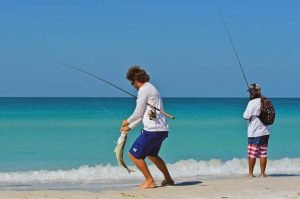 Two local young men on the beach fishing in the shallow water of the Gulf of Mexico