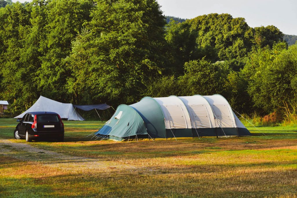 Campsite in the Belgian Ardennes with a tunnel tent on grass