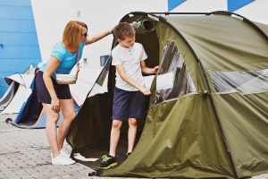 Woman and boy choose a camping tent in the store