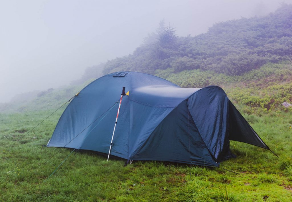 Green hybrid hiking tent after the storm with ajar entrance mounted on the mountain meadow in a heavy fog