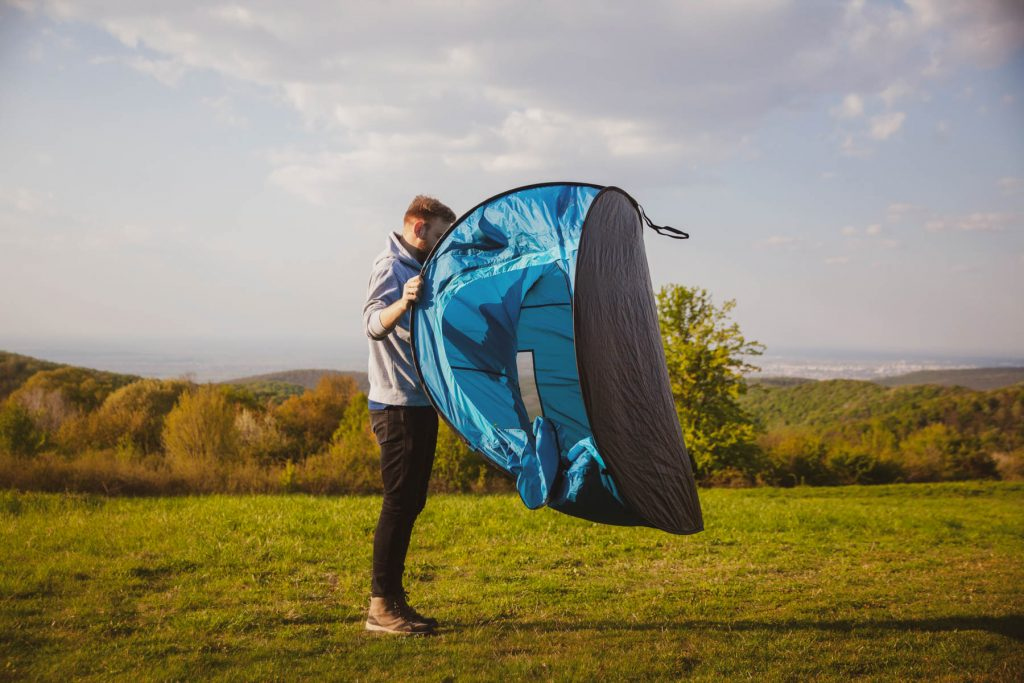 one young man, setting up a fast assembly tent, easy to set up.