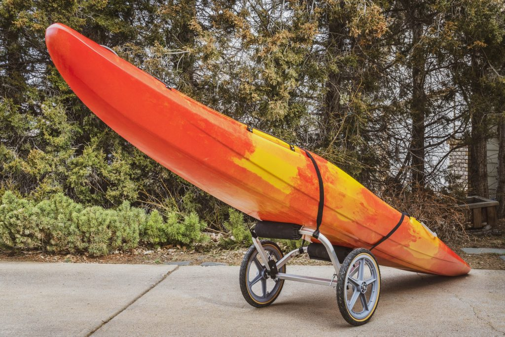 colorful river kayak on a folding cart in a driveway