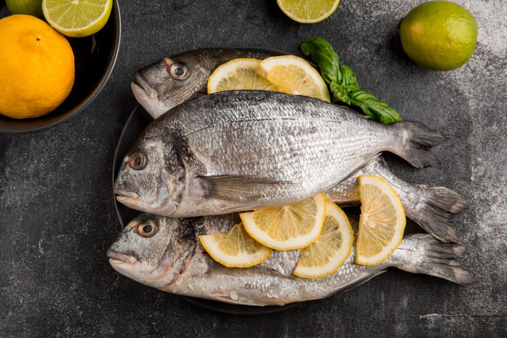 Uncooked seafood fish with slices of lemon