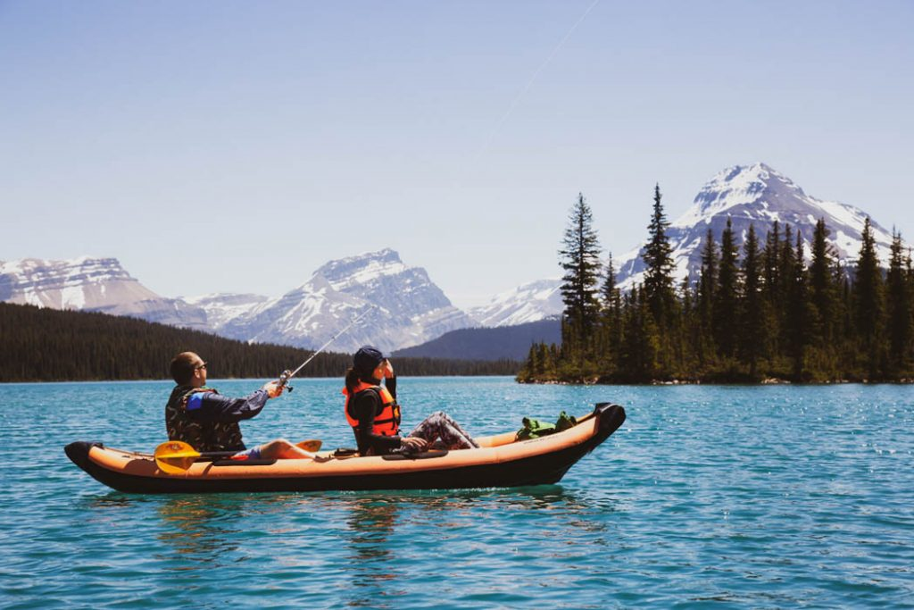 Couple of friends fishing on an inflatable kayak in a glacier lake
