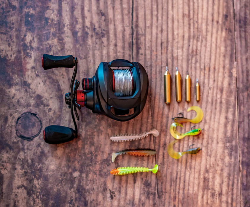 focus on baitcaster fishing reel with soft and out of focus lures and drop shot weights
