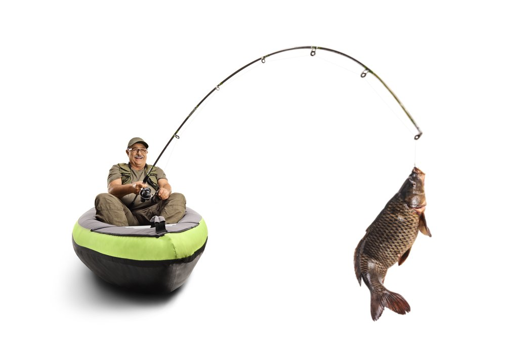 A man catching a fish from a kayak with his fishing rod