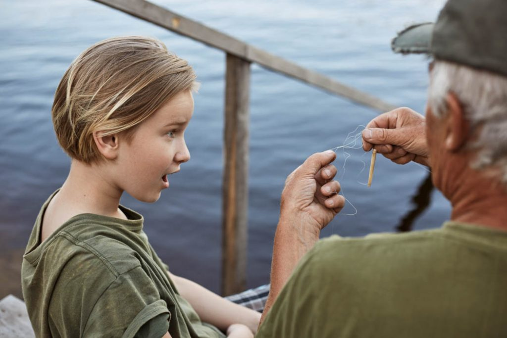 Father and son fixing tangled fishing line