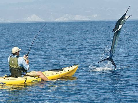 A man fishing in saltwater while on a kayak
