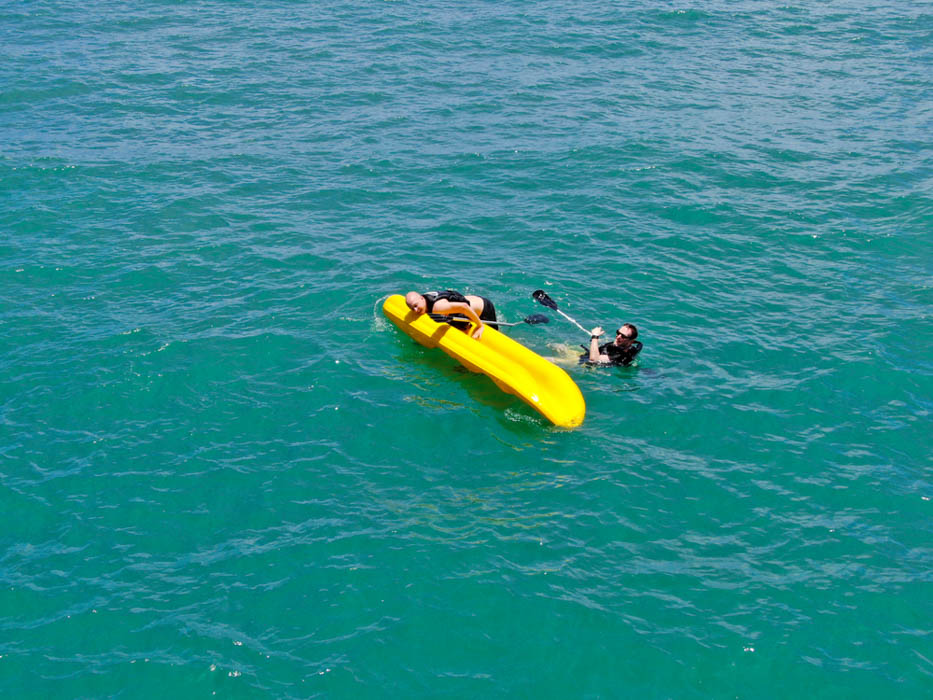 Aerial view view of strong young active men capsizing with their kayak on the clear blue turquoise water of the ocean