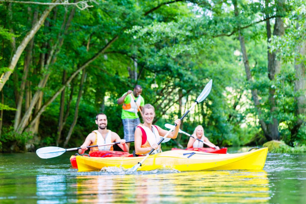 Friends paddling with kayak on forest river