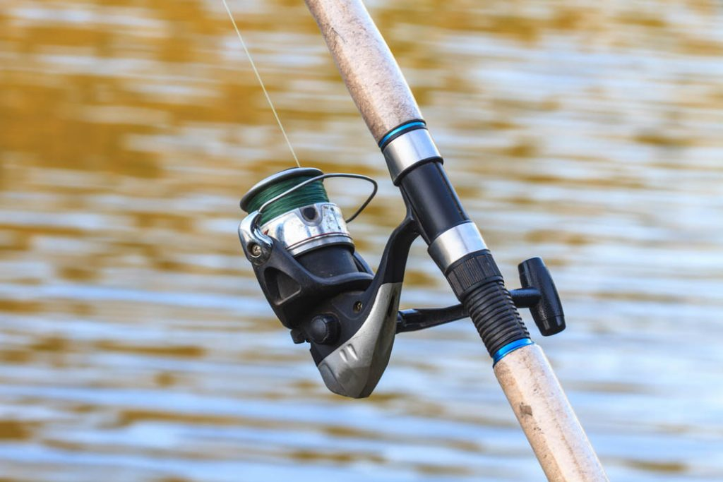 Fishing rod with spinning reel on riverside