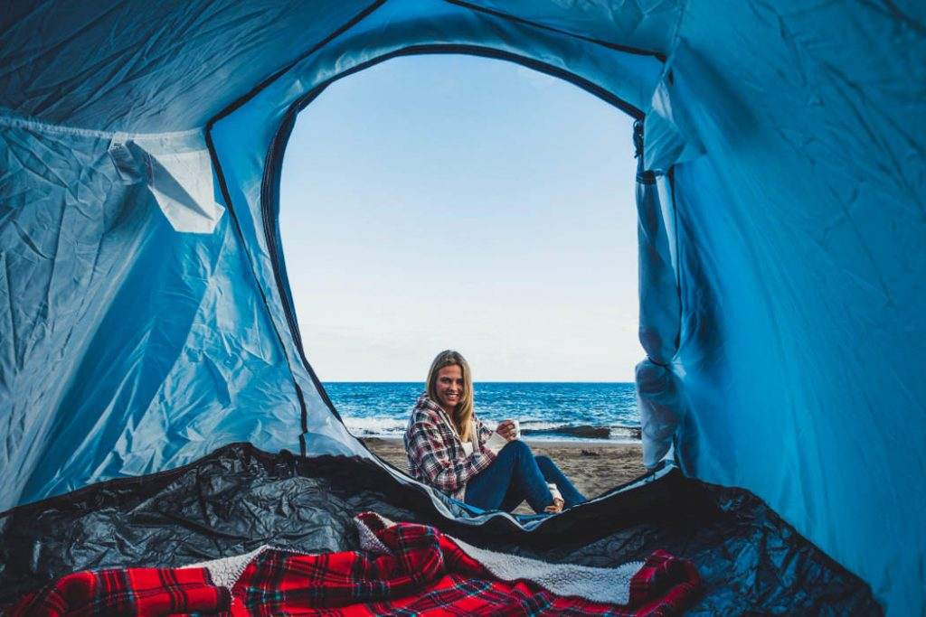 Blond girl viewed from inside a tent