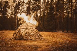 A beautiful shot of a tent with heating in the middle of the thick forest