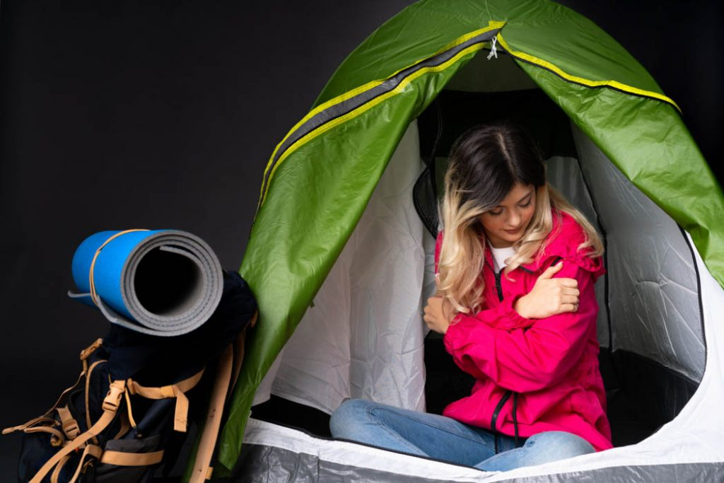 Teenager girl inside a camping green tent feeling cold