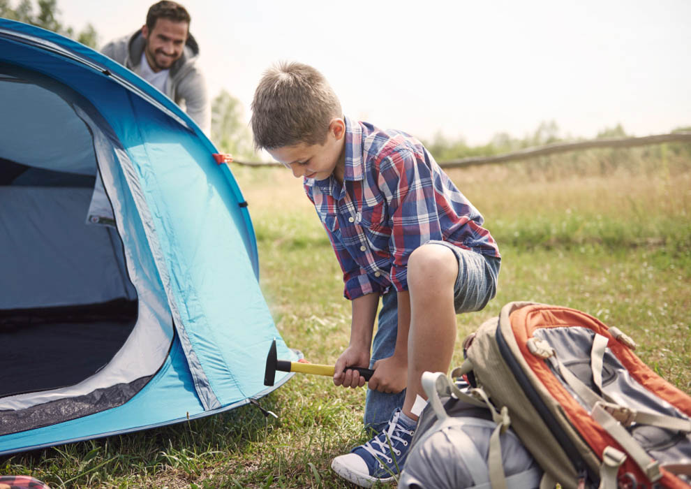 Helpful son on the camping with his father setting up a tent