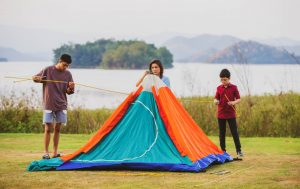 A mother and two sons joining to set up a tent for camping beside the wide lake