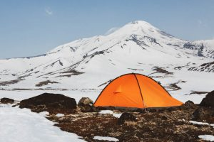 Orange tourist tent standing on meadow surrounded by snow