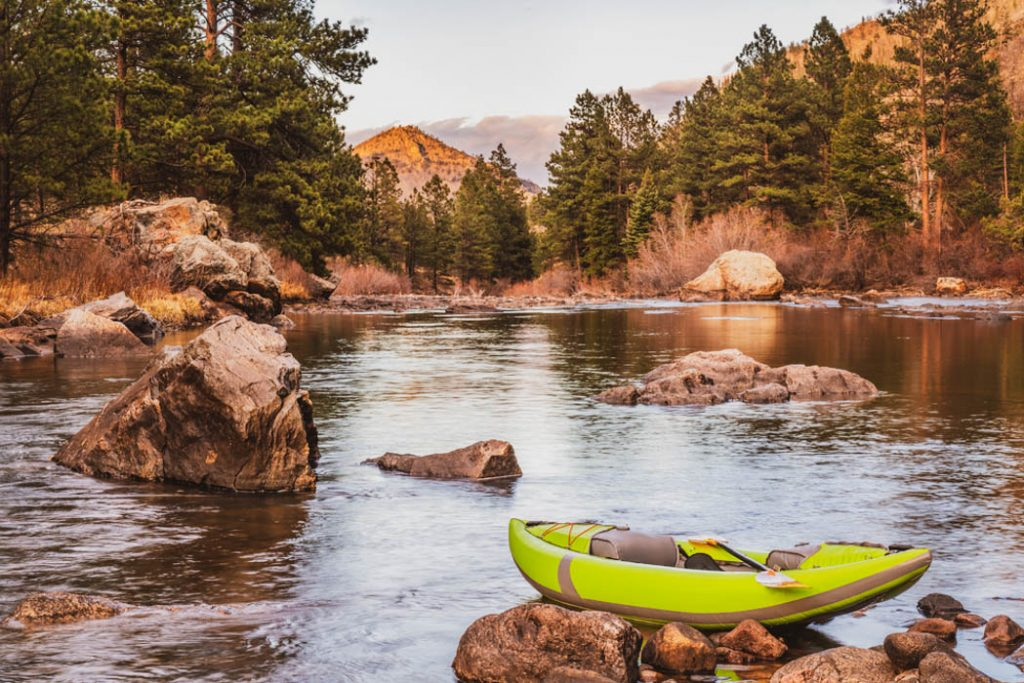 sunset over mountain river with an inflatable whitewater kayak