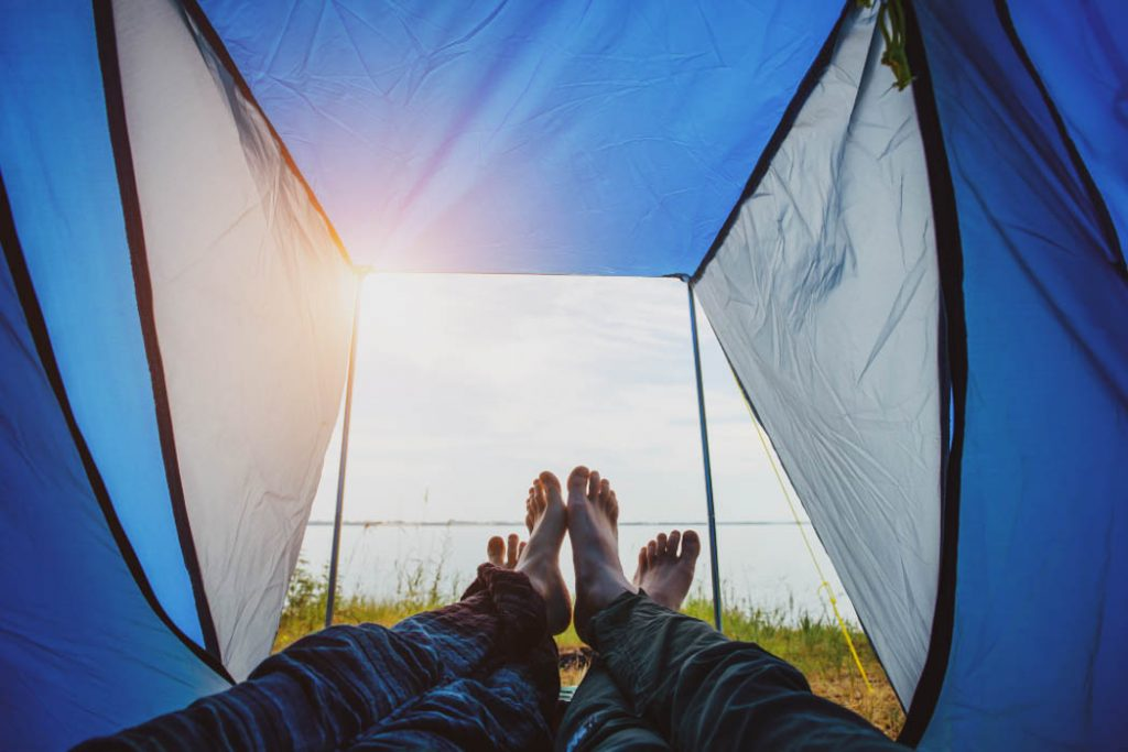 Bared legs of man and woman stretched out of tourist tent