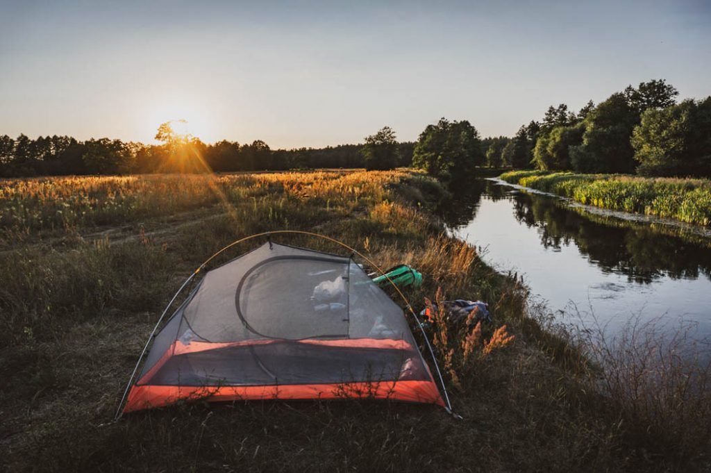 tent at sunset by the river, mosquito net