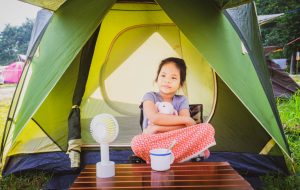 little girl sitting in front of tent with a fan
