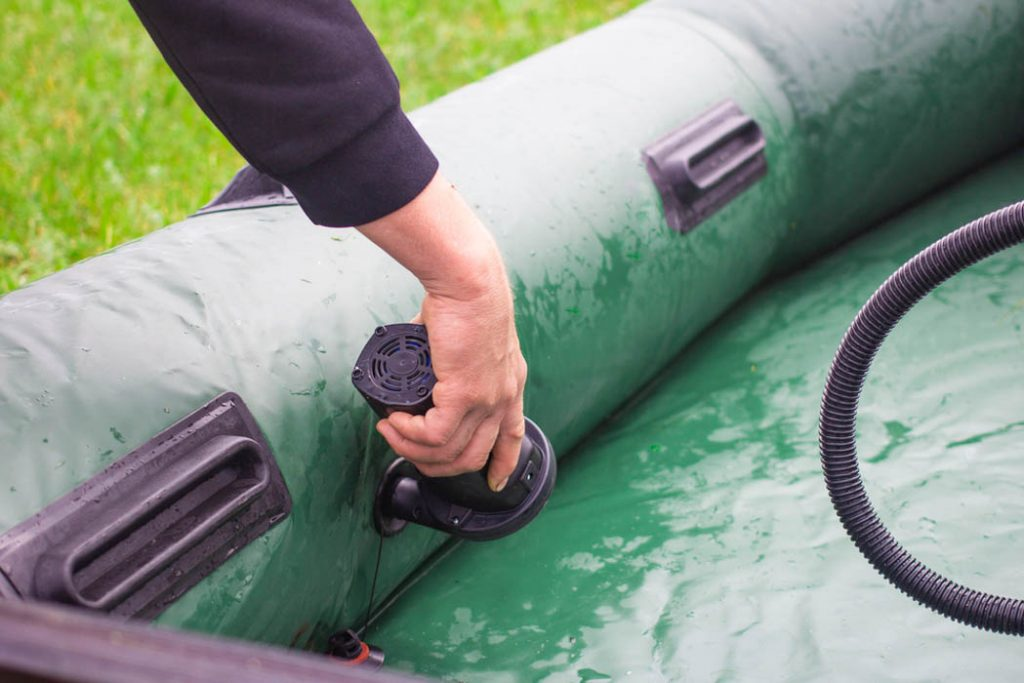 Man outdoors in nature inflating green rubber boat