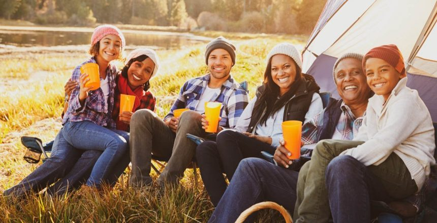 6 people sitting outside a tent