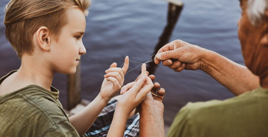 dad teaching his young son to untangle knot on fishing line