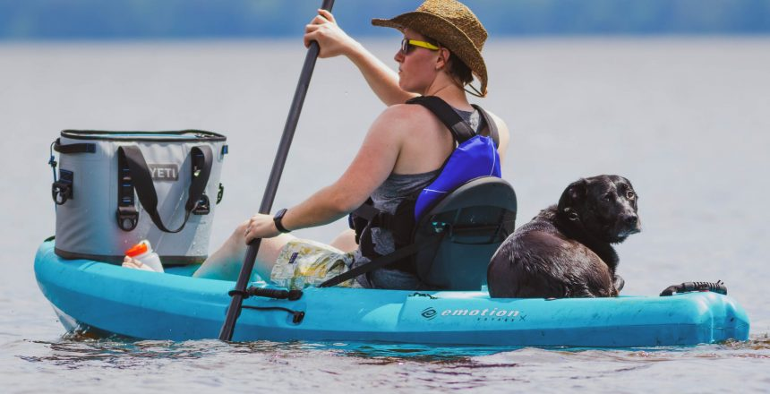 Young woman in kayak enjoys relaxing with her Yeti cooler