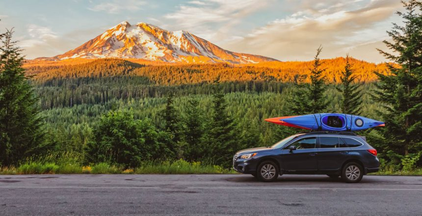 SUV with Kayaks in front of Mt. Adams at sunset