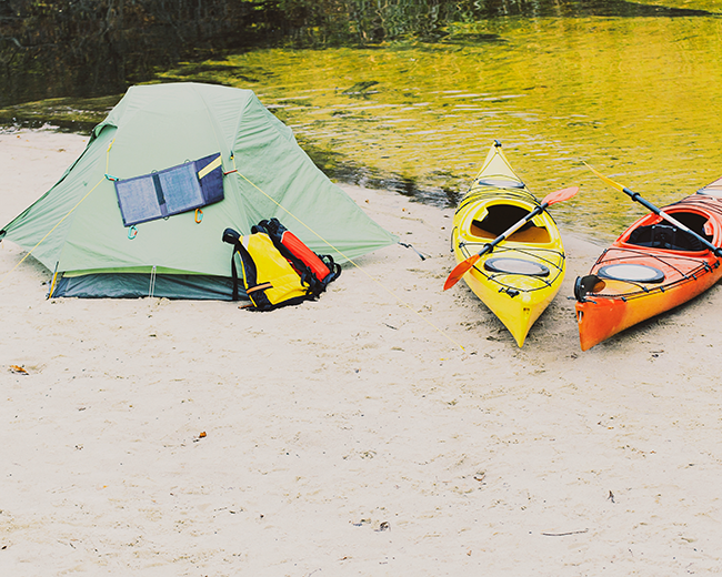 two kayaks with a tent next to river
