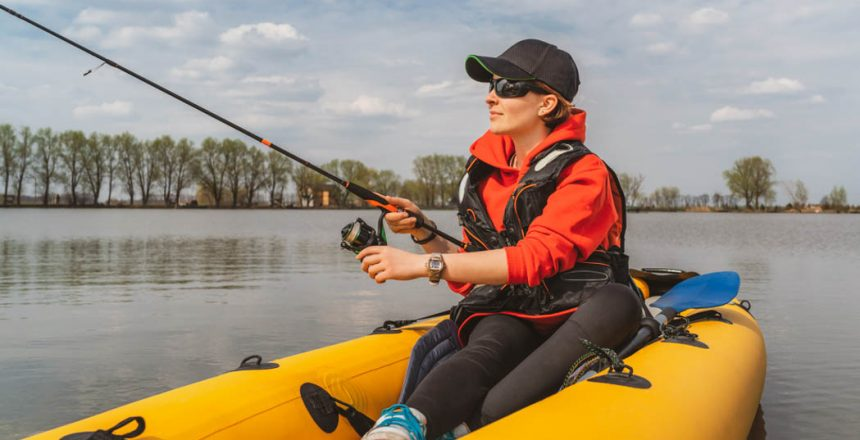 Fisherwoman on inflatable boat with fishing tackle